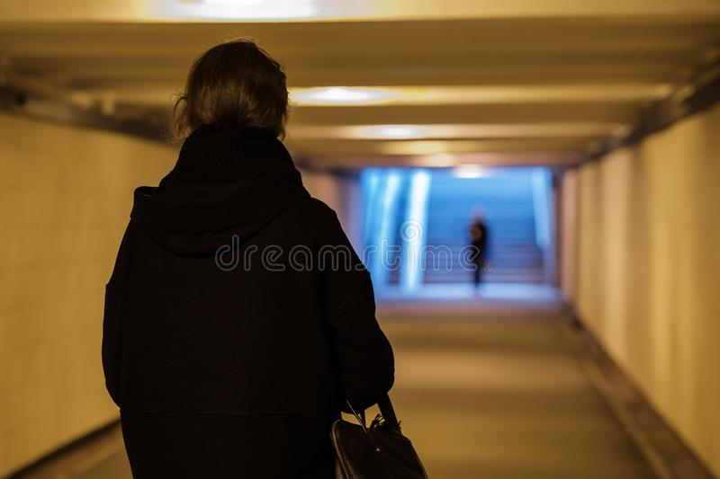A girl in black clothes is walking along an underground passage. HAving troubles in life because she is alone stock images