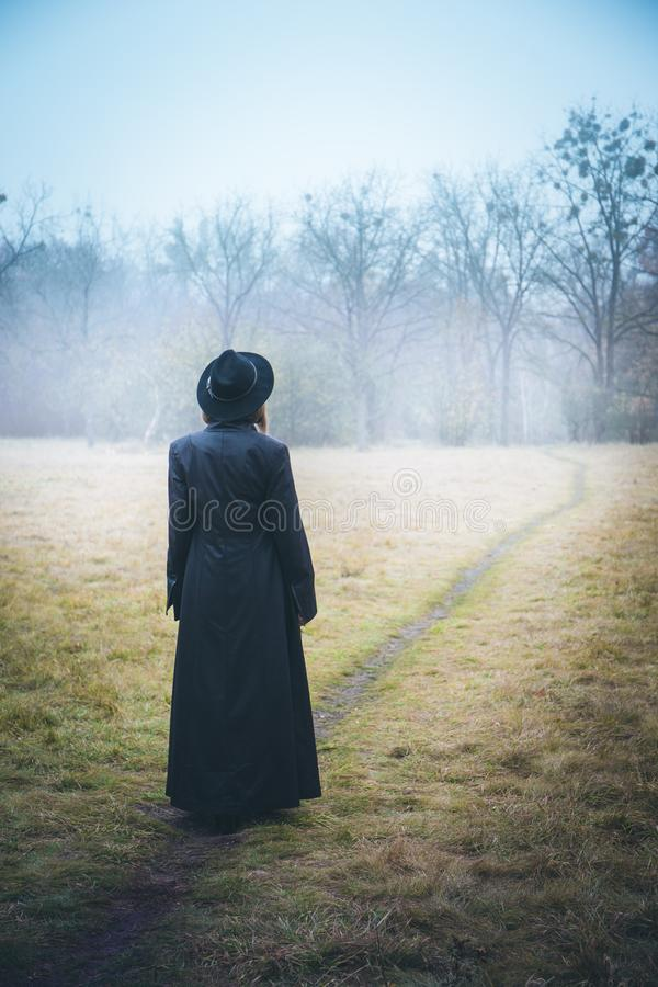 Girl in a black coat in the fog royalty free stock photography