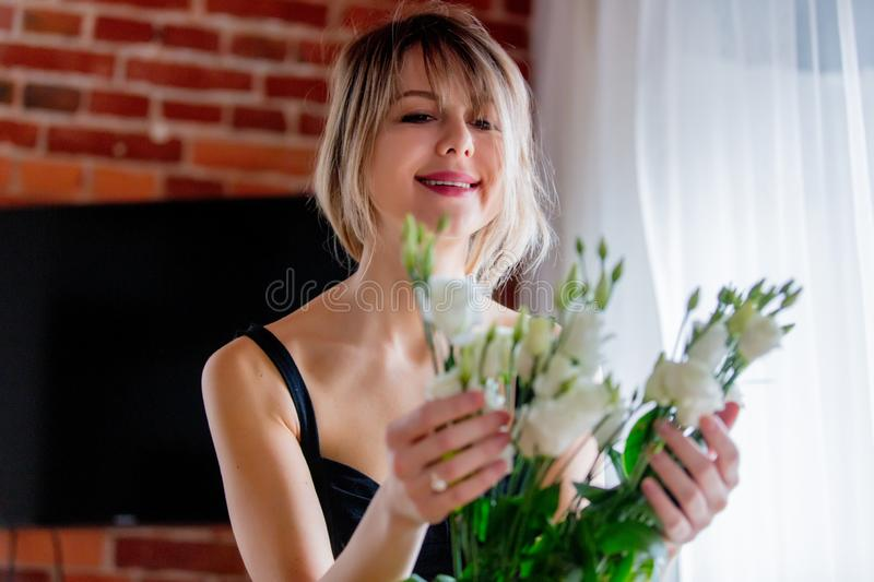 Girl in a black dress is holding white roses before putting them in a vase stock photo