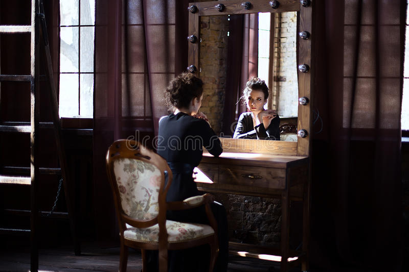 Girl in black dress looking in the mirror stock photo