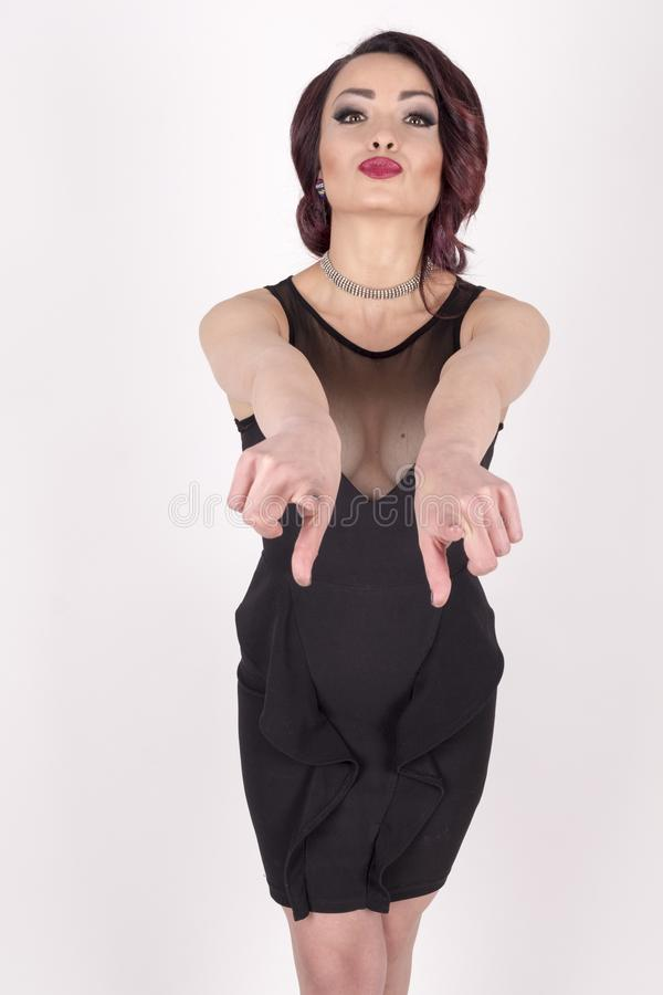 A girl in an black dress pointing forwards. Beautiful girl in an elegant black dress pointing forwards with her hands stock photo