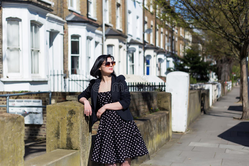 Girl in black dress with polka dots and sunglasses royalty free stock photography