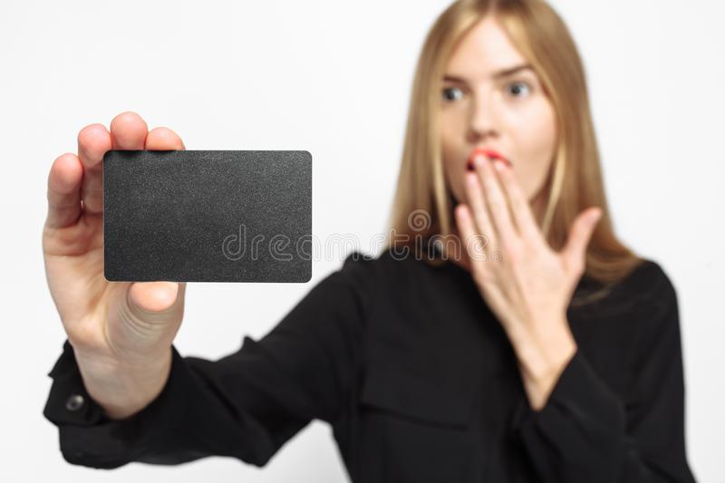 girl in black dress and with red lips, with credit card in hand, shocked looking at, card, white background, black Friday, stock photos