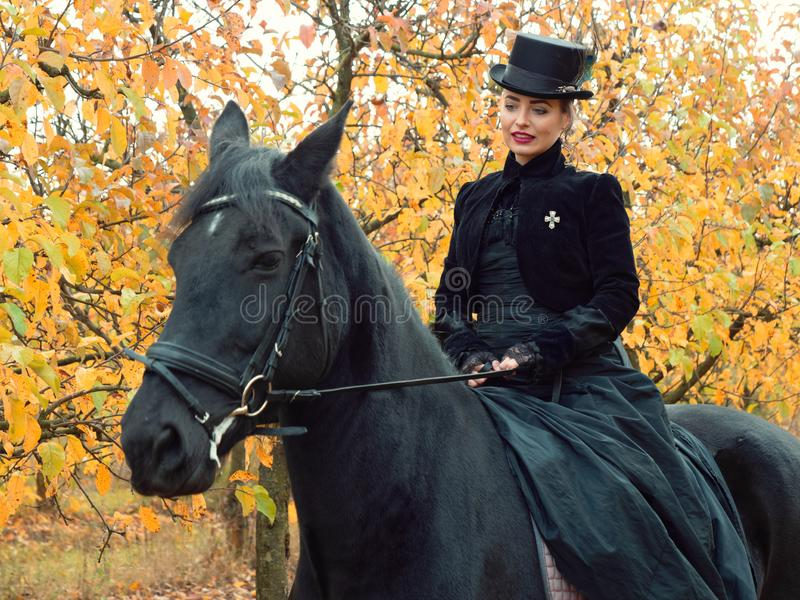 Girl in a black dress riding a black horse. 2019 royalty free stock image