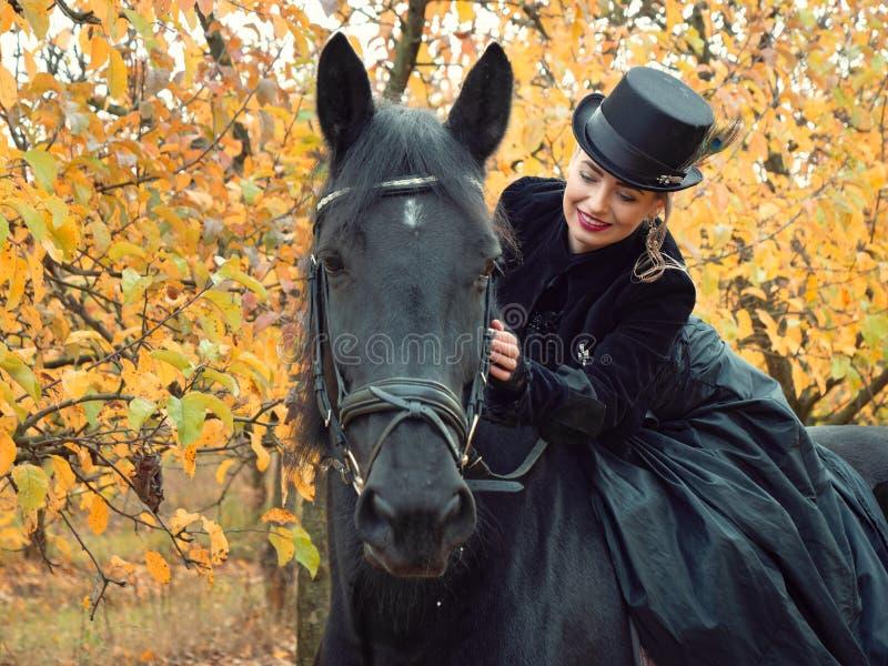 Girl in a black dress riding a black horse. 2019 royalty free stock photos