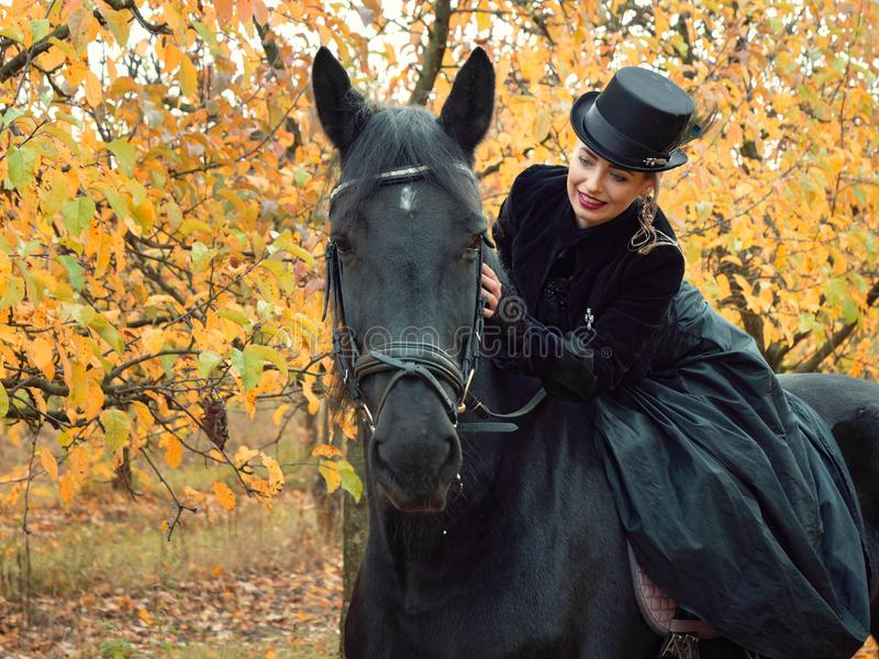 Girl in a black dress riding a black horse. 2019 stock photo