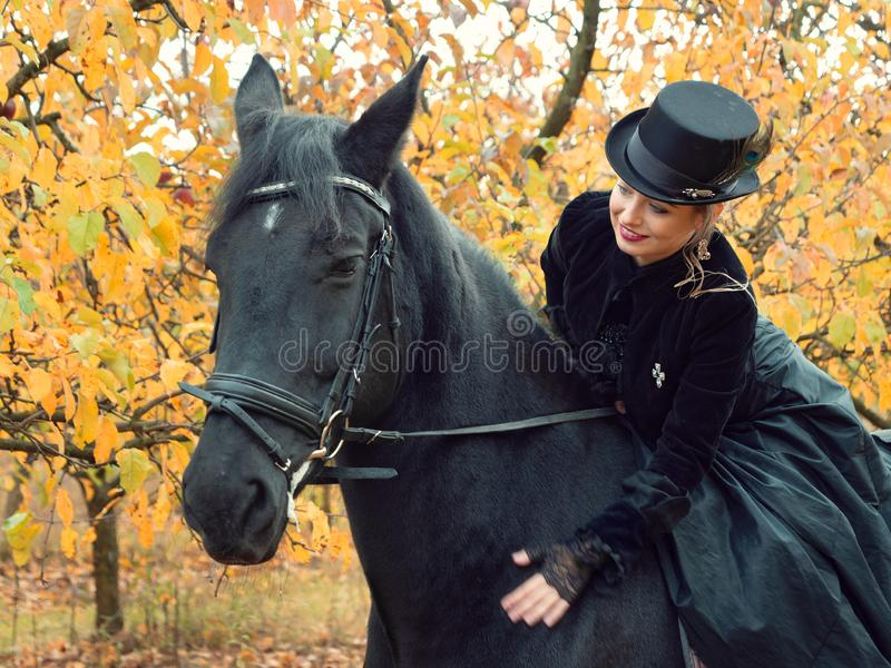 Girl in a black dress riding a black horse. 2019 stock images