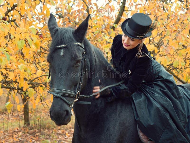 Girl in a black dress riding a black horse. 2019 stock photos
