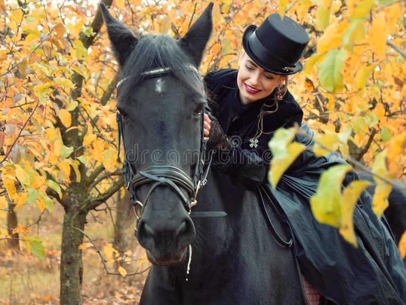 Girl in a black dress riding a black horse. 2019 royalty free stock photo