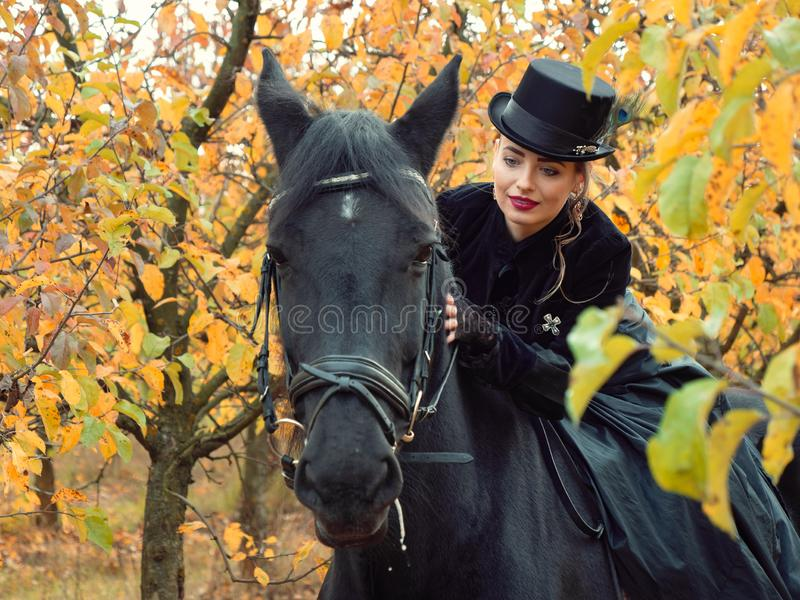 Girl in a black dress riding a black horse. 2019 royalty free stock images
