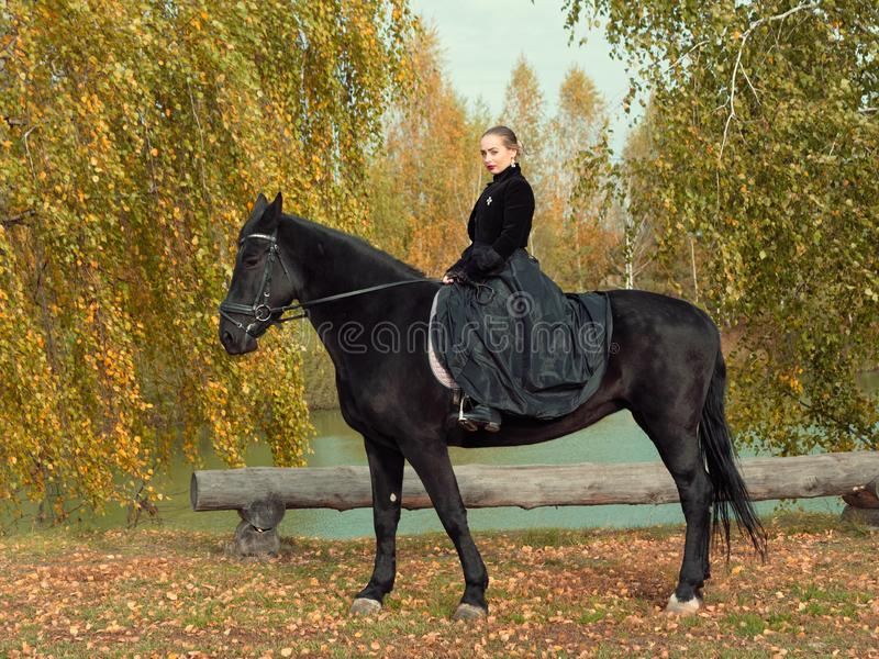 Girl in a black dress riding a black horse. 2019 royalty free stock photography