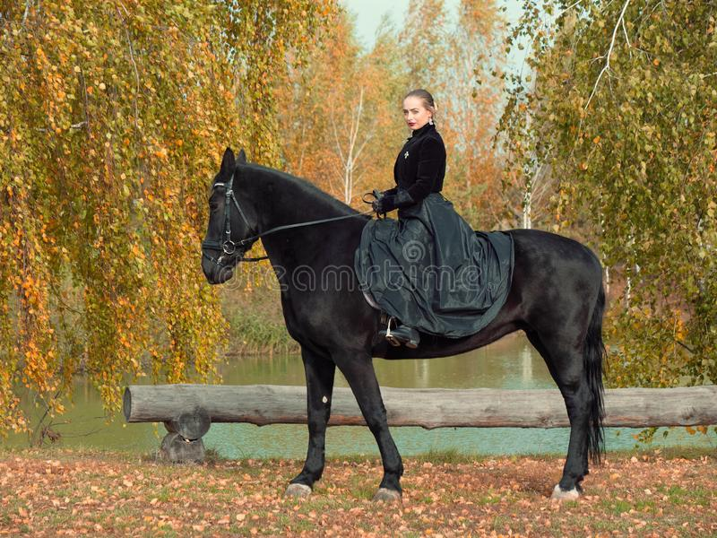 Girl in a black dress riding a black horse. 2019 stock image