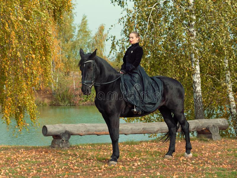 Girl in a black dress riding a black horse. 2019 stock photography