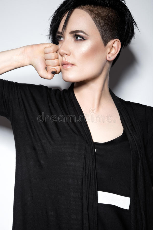 Girl in a black dress with shaved head, art gothic style. Girl in a black dress with shaved head in art gothic style. Picture taken in the studio on a white stock image
