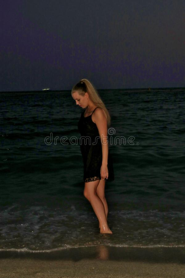 Girl in a black dress on the shore by the sea in the evening royalty free stock photos