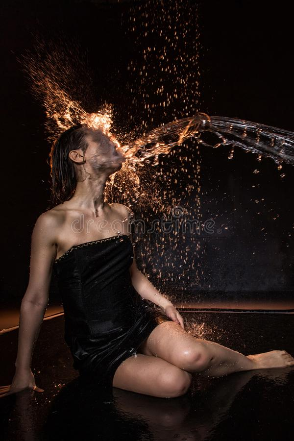 Girl in black dress in water in a small pool, stream of water flying to her and black background stock images
