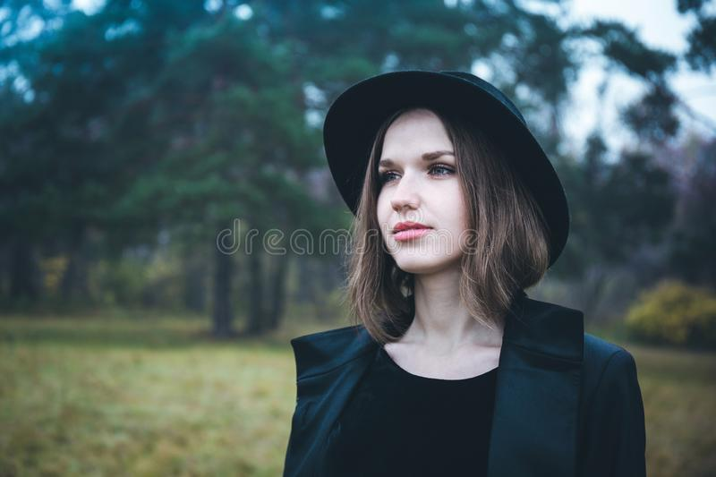Girl in a black hat in the gloomy forest royalty free stock photos