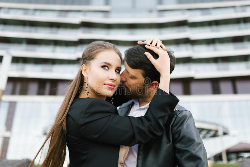 A girl in a black jacket embraces a man behind the head, who is dressed in a black. A girl in a black jacket embraces a men behind the head, who is dressed in a royalty free stock images