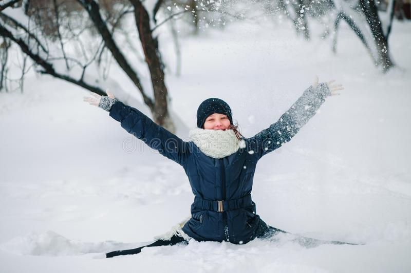 girl in a black jacket and a black hat sits on a string in the snow and throws snow. Happy child after a snowfall. Snow on the tre stock photos