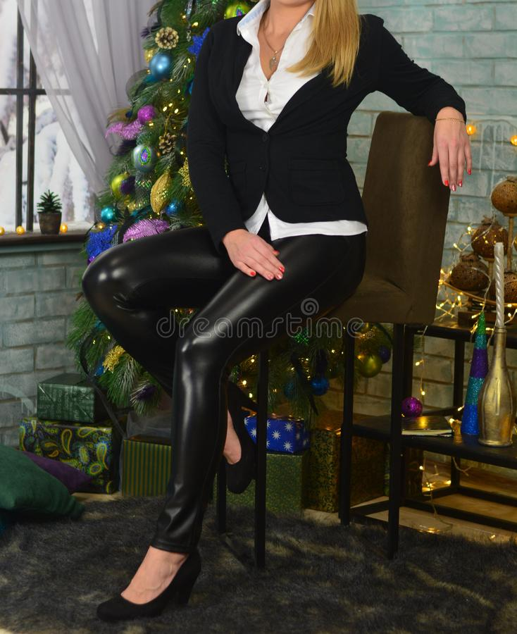 The girl in a black jacket, white shirt and black lacquer pants sits on a chair against the background of a Christmas tree and a b stock photo
