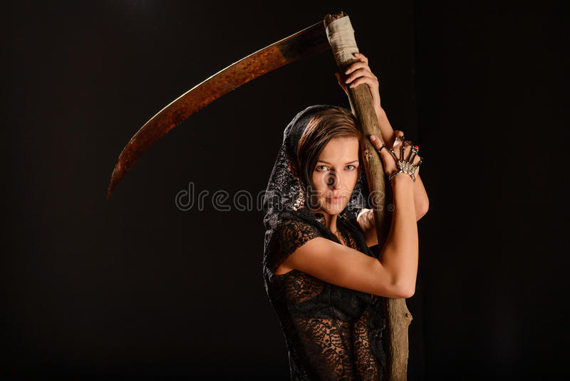 Girl in a black lace smock with scythe of death. Girl in a black lace smock with a scythe of death. concept royalty free stock images