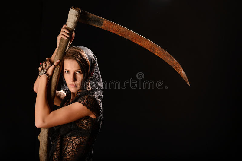 Girl in a black lace smock with scythe of death. Girl in a black lace smock with a scythe of death. concept royalty free stock photos