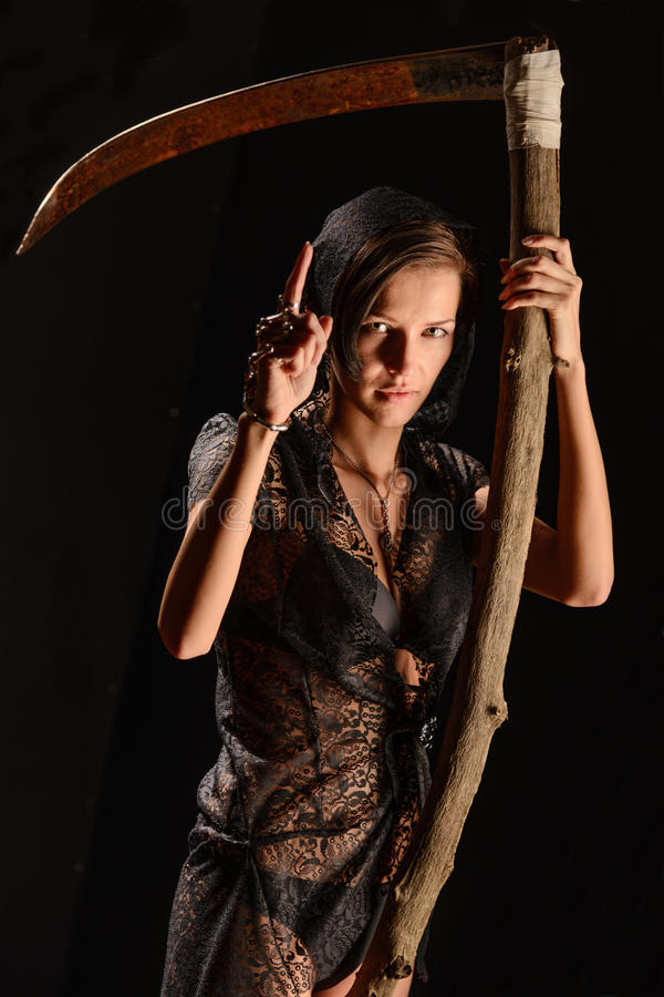 Girl in a black lace smock with scythe of death. Girl in a black lace smock with a scythe of death. concept stock photos