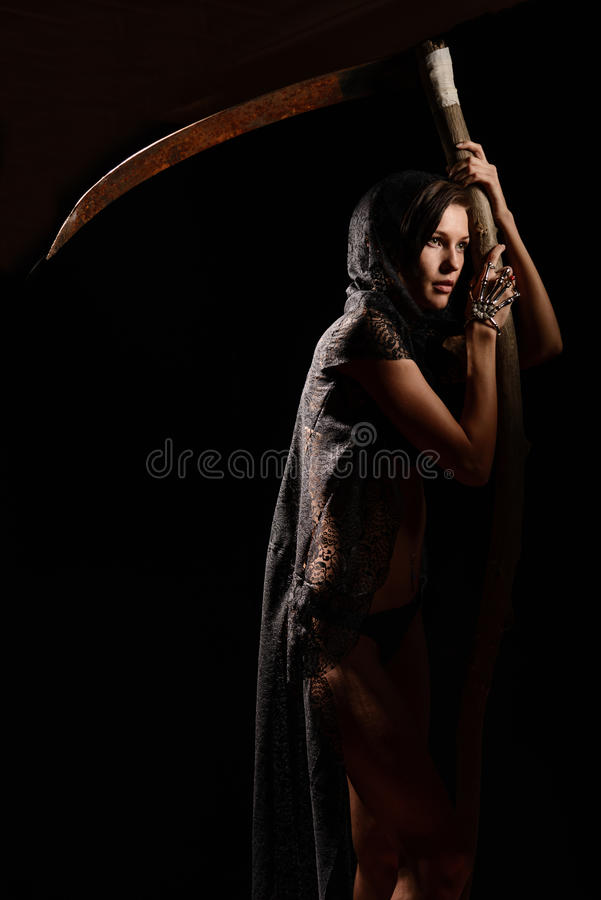 Girl in a black lace smock with scythe of death. Girl in a black lace smock with a scythe of death. concept stock image