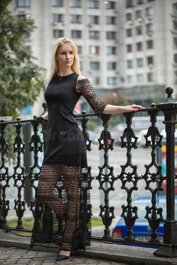 Girl in a black long dress near forged fence. Autumn in Kyiv stock photography