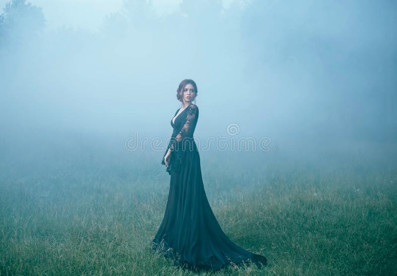 A girl in a black long dress walking along ia a clearing in thick fog. scared, beautiful, witch ia going to the forest royalty free stock photography