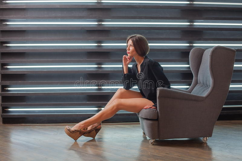 Girl in a black man`s shirt in his chair. royalty free stock photography