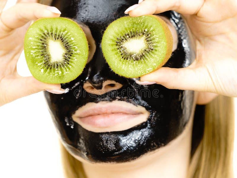 Girl black mask on face holds kiwi fruit. Young woman with carbo black peel-off mask on her face holding kiwi fruit halves, covering eyes, on white. Beauty stock image