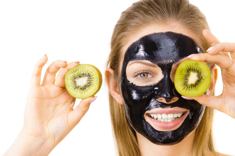 Girl black mask on face holds kiwi fruit. Young woman with carbo black peel-off mask on her face holding kiwi fruit halves, covering eyes, on white. Beauty royalty free stock image