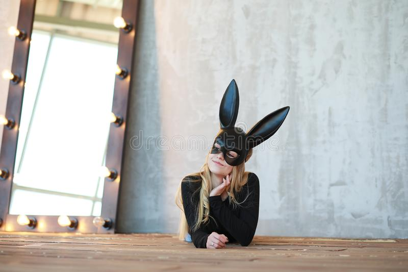 A girl in a black mask. With long ears in the studior stock images