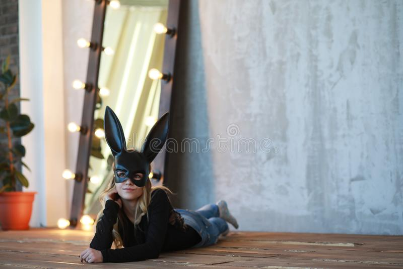 A girl in a black mask. With long ears in the studior royalty free stock photos