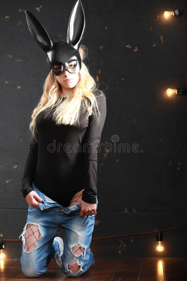 A girl in a black mask. With long ears in the studior stock photography