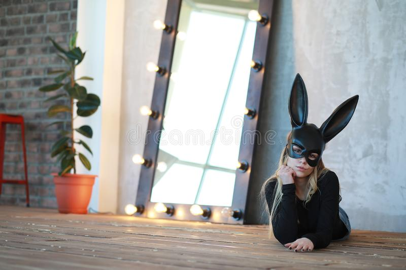 A girl in a black mask. With long ears in the studior stock photo