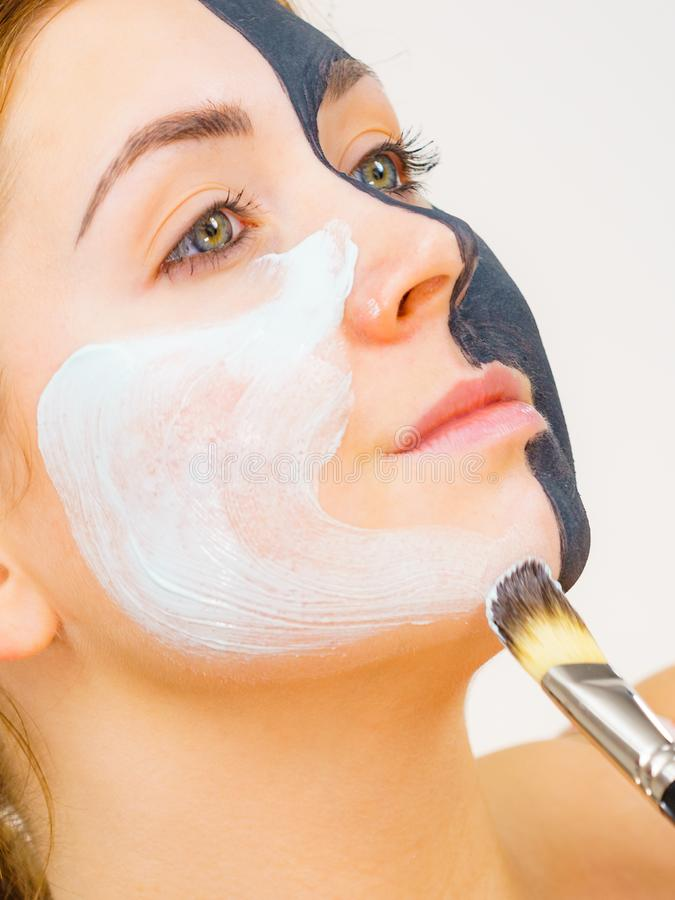 Girl black mask on half face apply white mud. Woman with clay carbo black mask on half face applying white mud to clean skin. Girl taking care of oily complexion royalty free stock images
