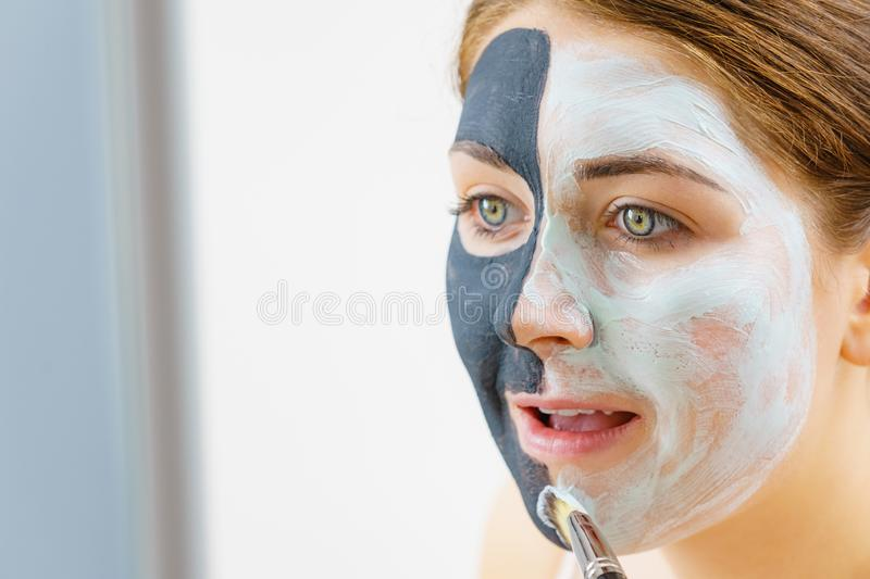 Girl black mask on half face apply white mud. Woman with clay carbo black mask on half face applying white mud to clean skin. Girl taking care of oily complexion royalty free stock photography