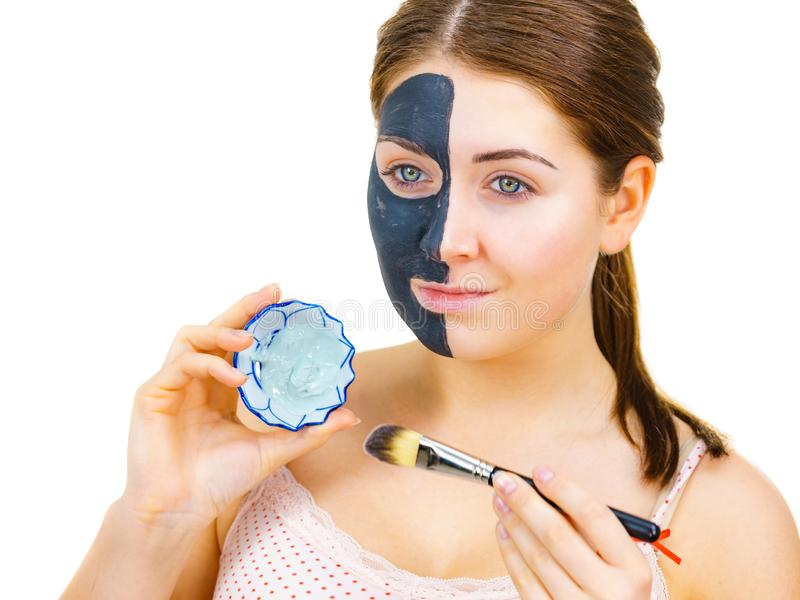 Girl black mask on half face apply white mud. Woman with clay carbo black mask on half face applying white mud to clean skin. Girl taking care of oily complexion stock images