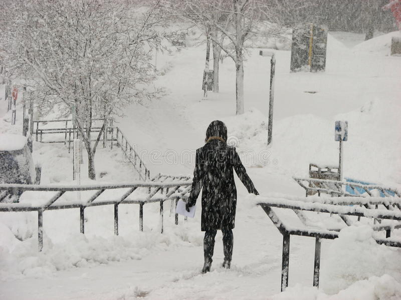 A girl in black outfit in heavy Snow Storm at UWM. A girl in black overcoat passing through foot over bridge in heavy Snow Storm Milwaukee, Wisconsin, USA royalty free stock photos