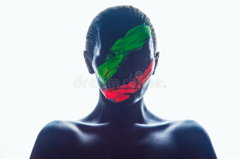 Girl with a black paint on the face. Green and red stock photos