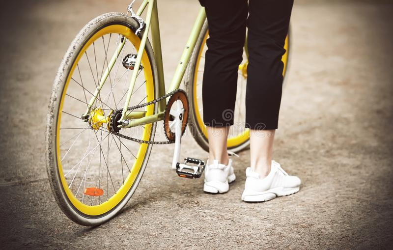 A girl stands near her beautiful bike is yellow-green royalty free stock photos