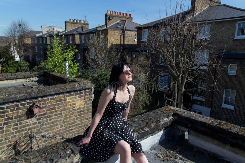 Girl in black polka dot dress sitting on the roo stock photos