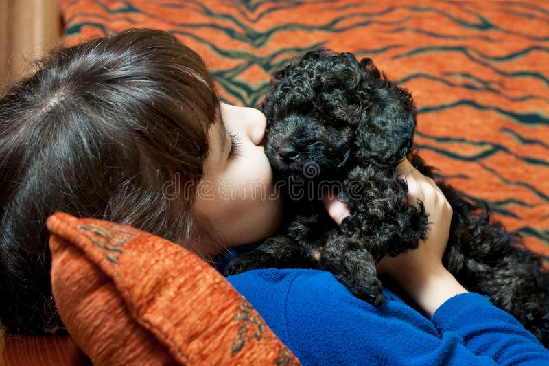 Girl with a black puppy stock images