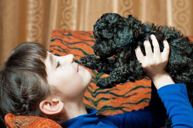 Girl with a black puppy stock photos