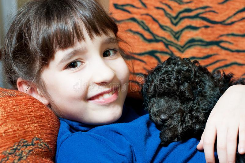 Girl with a black puppy stock image