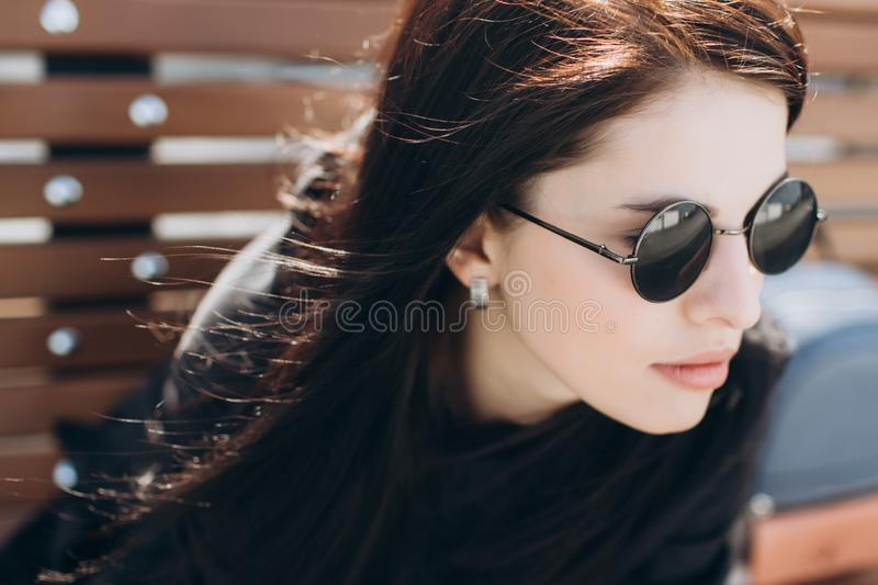 The girl in black round glasses looks ahead stock image