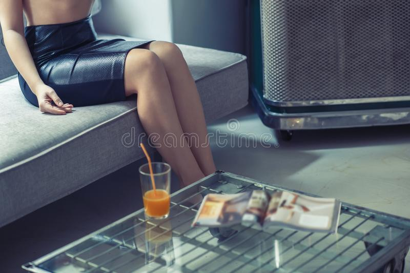A girl in a black skirt sits on a sofa near a table with a glass of juice and a magazine. A girl in a black skirt sits on a sofa near a table with a glass of royalty free stock photos