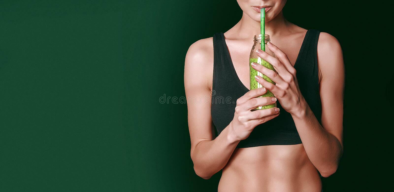 A girl in a black sports top holds a jar of vegetable smoothies in her hands royalty free stock photo